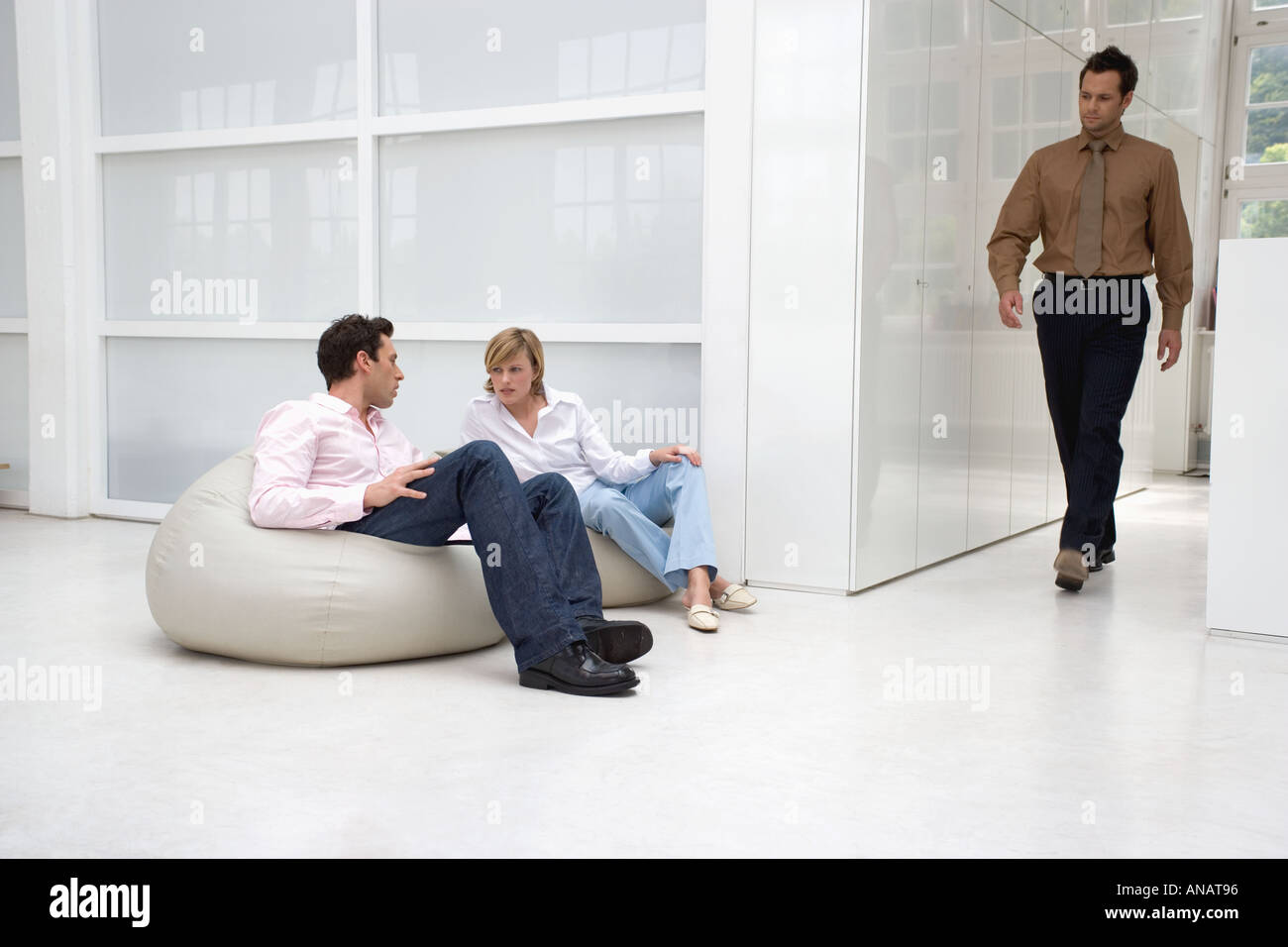 man passing by couple on bean bags in office building - Stock Image