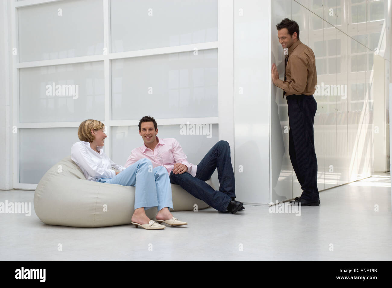 man hiding from two business colleagues in office building - Stock Image