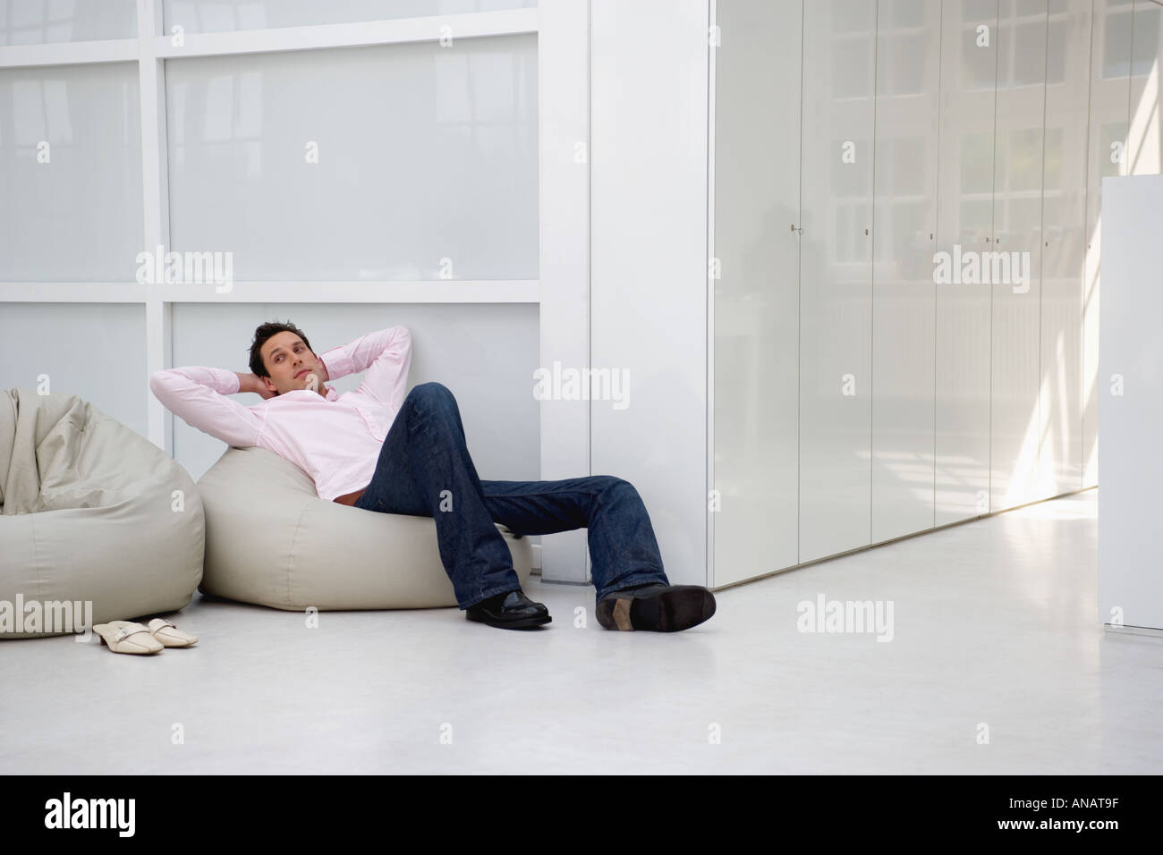 man sitting comfortably relaxing on bean bag in office rest area - Stock Image