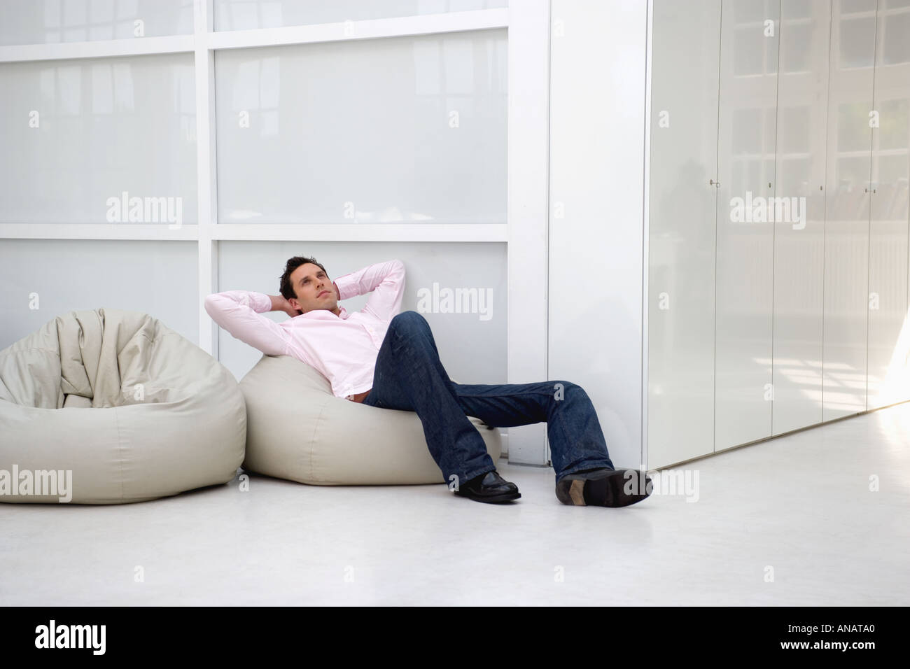 young businessman day dreaming on bean bag in office - Stock Image