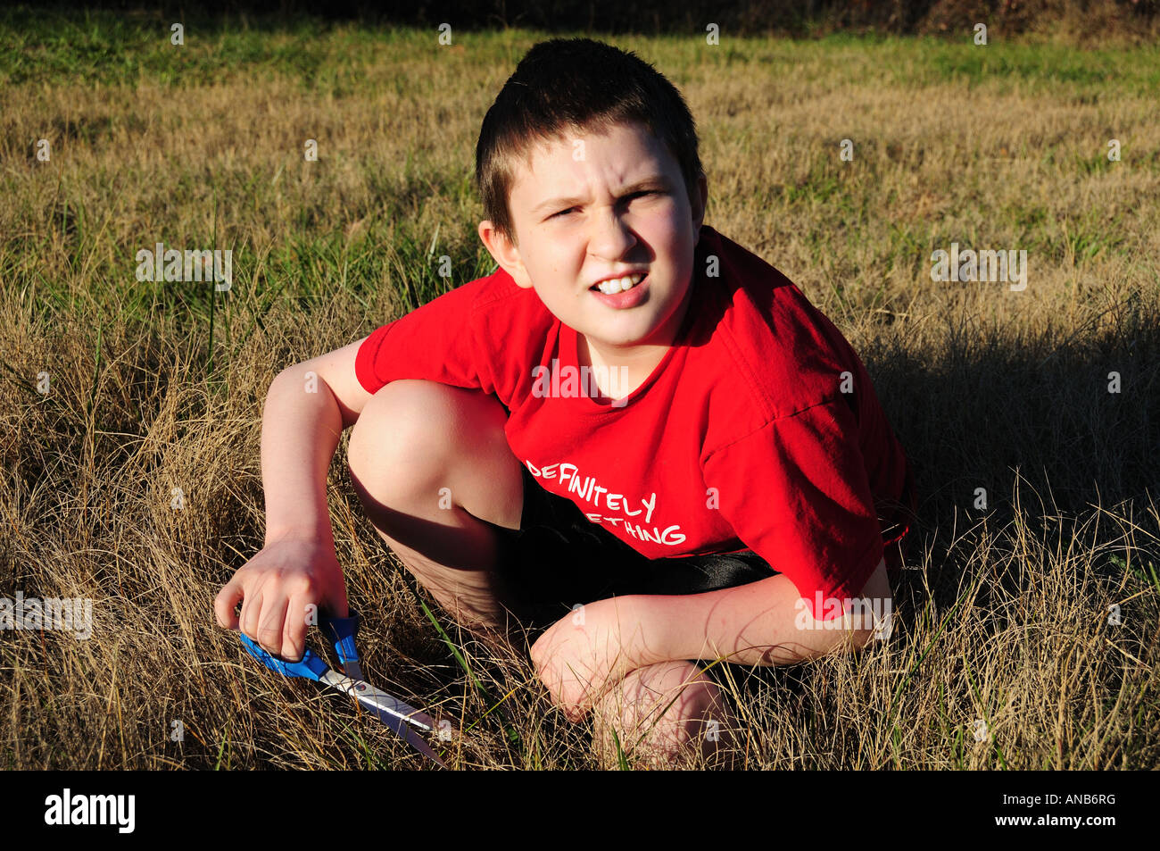A young boy cuts the grass the slow way, one blade at a time. Symbolizes the concept of hard detail at work or a - Stock Image