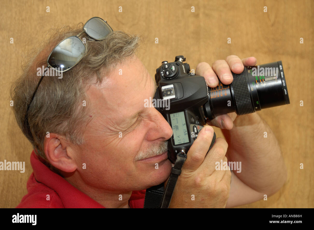 A professional photographer tests a brand new digital SLR camera with a macro lens mounted. - Stock Image