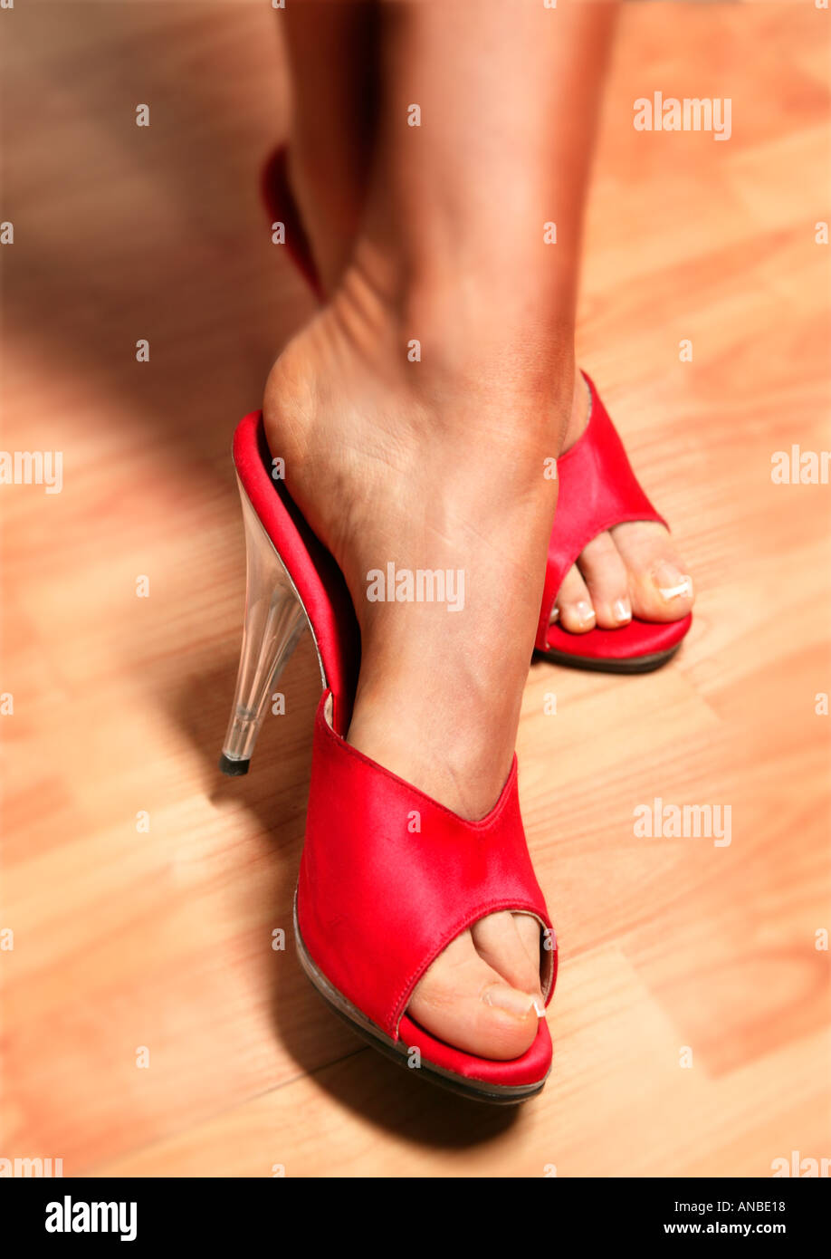Lady in red shoes on wooden floor Stock Photo