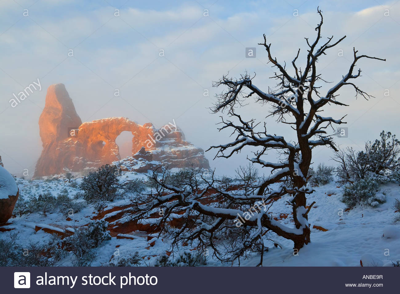 Turret Arch, shrouded in fog, is lit by the rising sun after a night of fresh snowfall in Arches National Park near - Stock Image