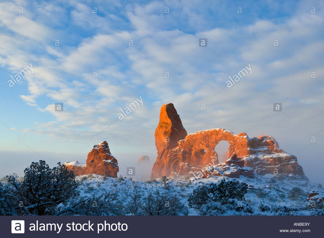 Turret Arch, a prominent natural arch in Arches National Park, Utah, is lit by the rising sun on a foggy winter - Stock Image