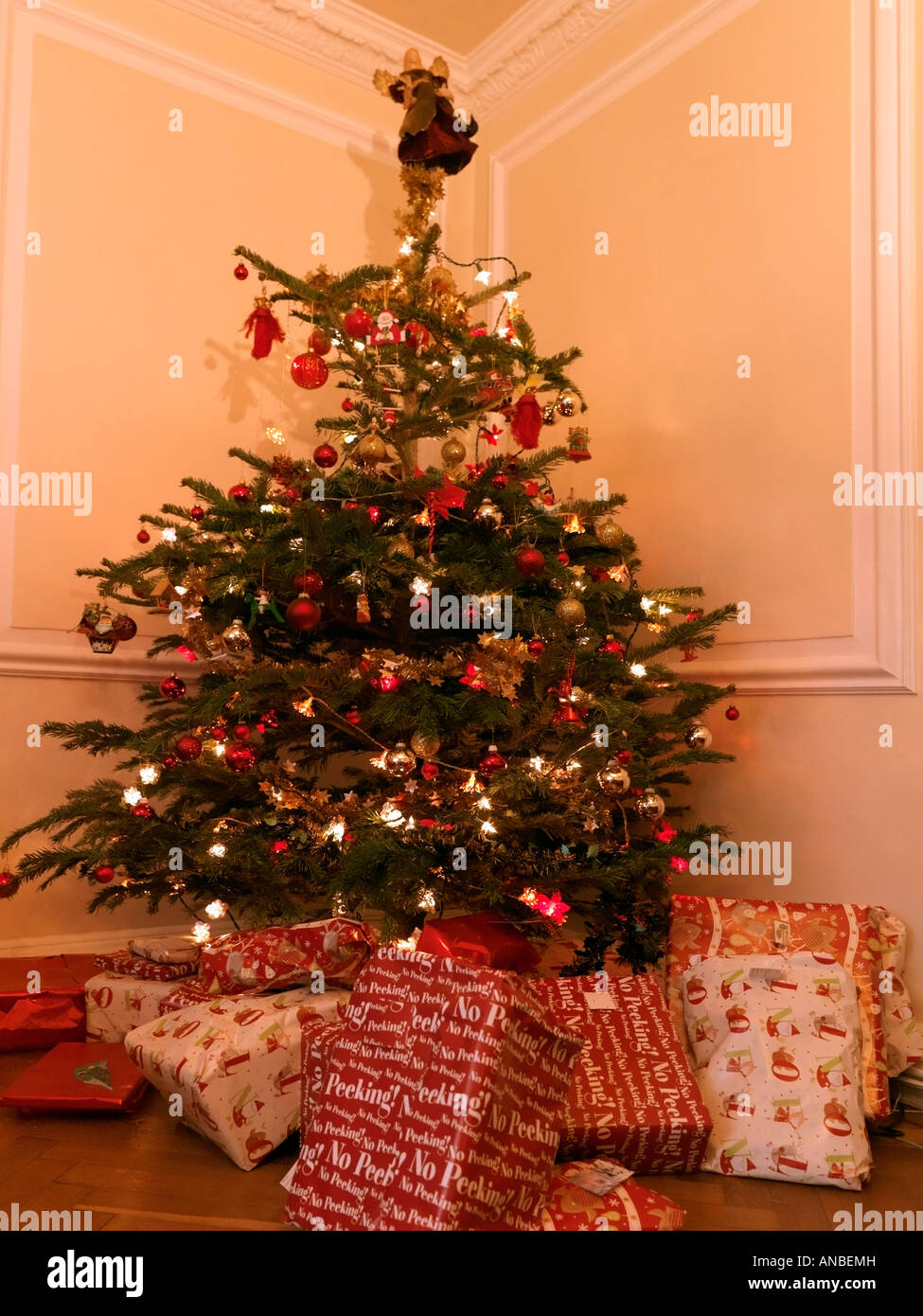 Christmas Tree With Presents And Angel On Top In Lounge Stock Photo