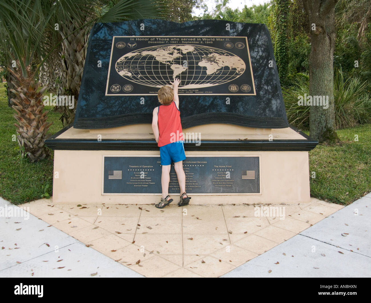 boy looking at touching world war two WWII two memorial monument world map learning education history freedom - Stock Image