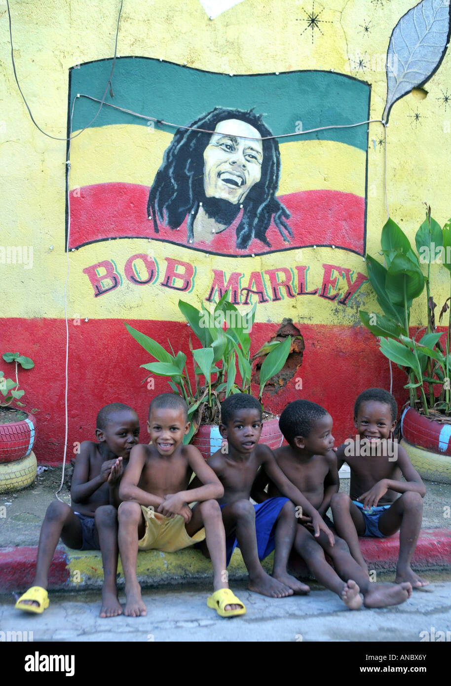 Jamaica, Kingston, children sitting under a wallpainting of Bob Marley - Stock Image