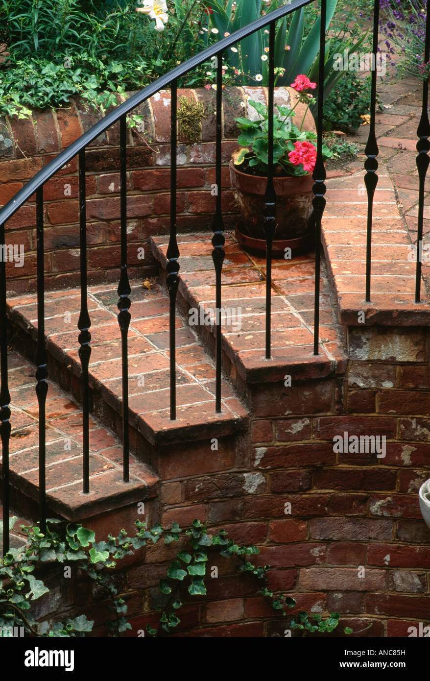 Close up of brick steps and black cast iron railings in town garden - Stock Image