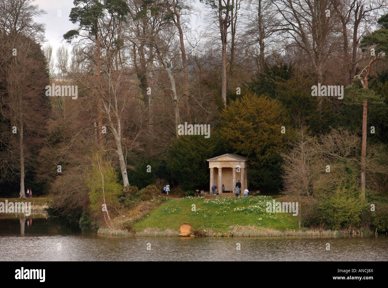 VISITORS IN THE GROUNDS OF BOWOOD HOUSE EXPLORE THE DORIC TEMPLE WHICH SITS BESIDE THE LAKE WILTSHIRE UK Stock Photo