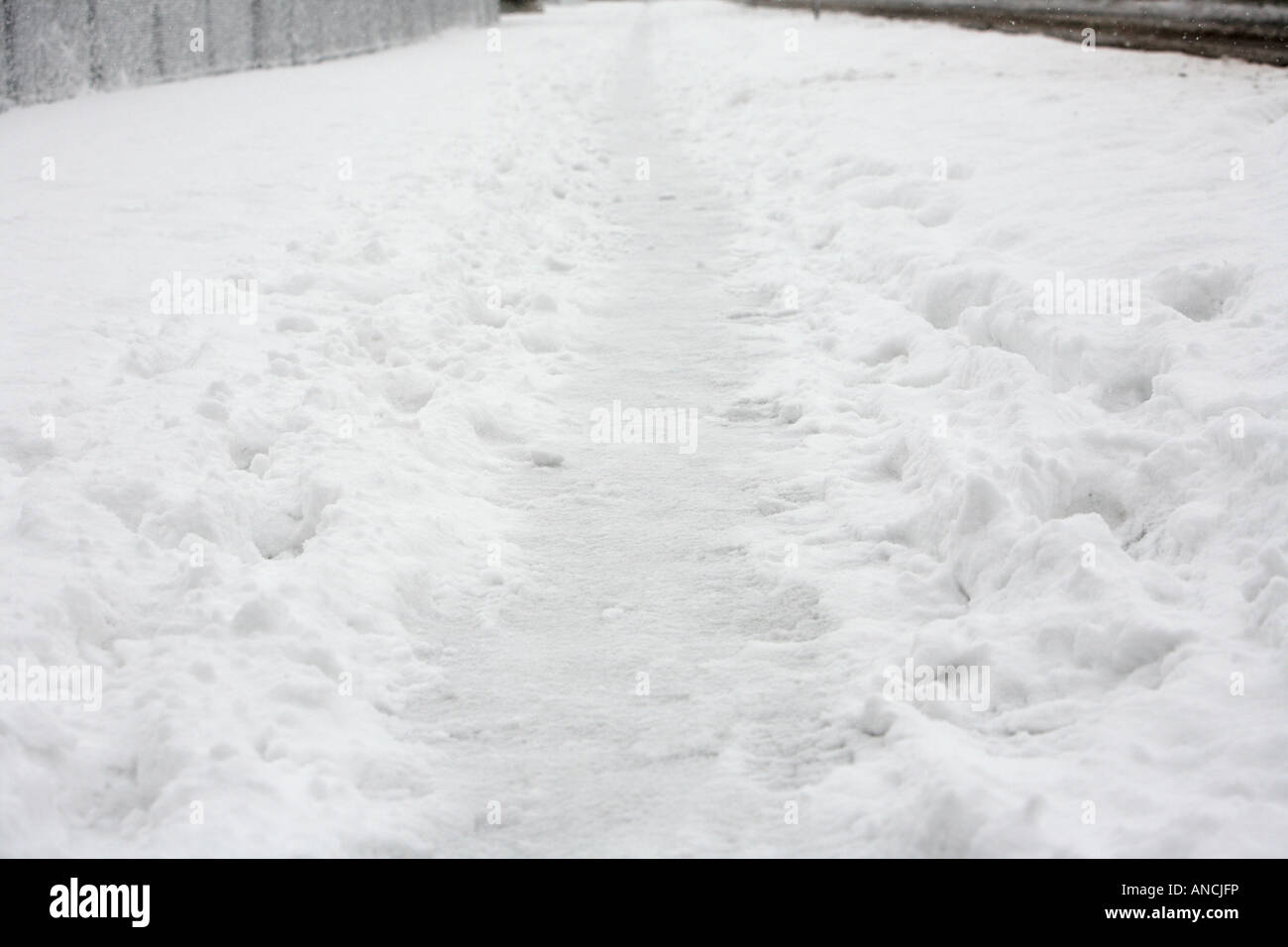 path worn through the snow on footpath creating icy path with footprints slippy - Stock Image