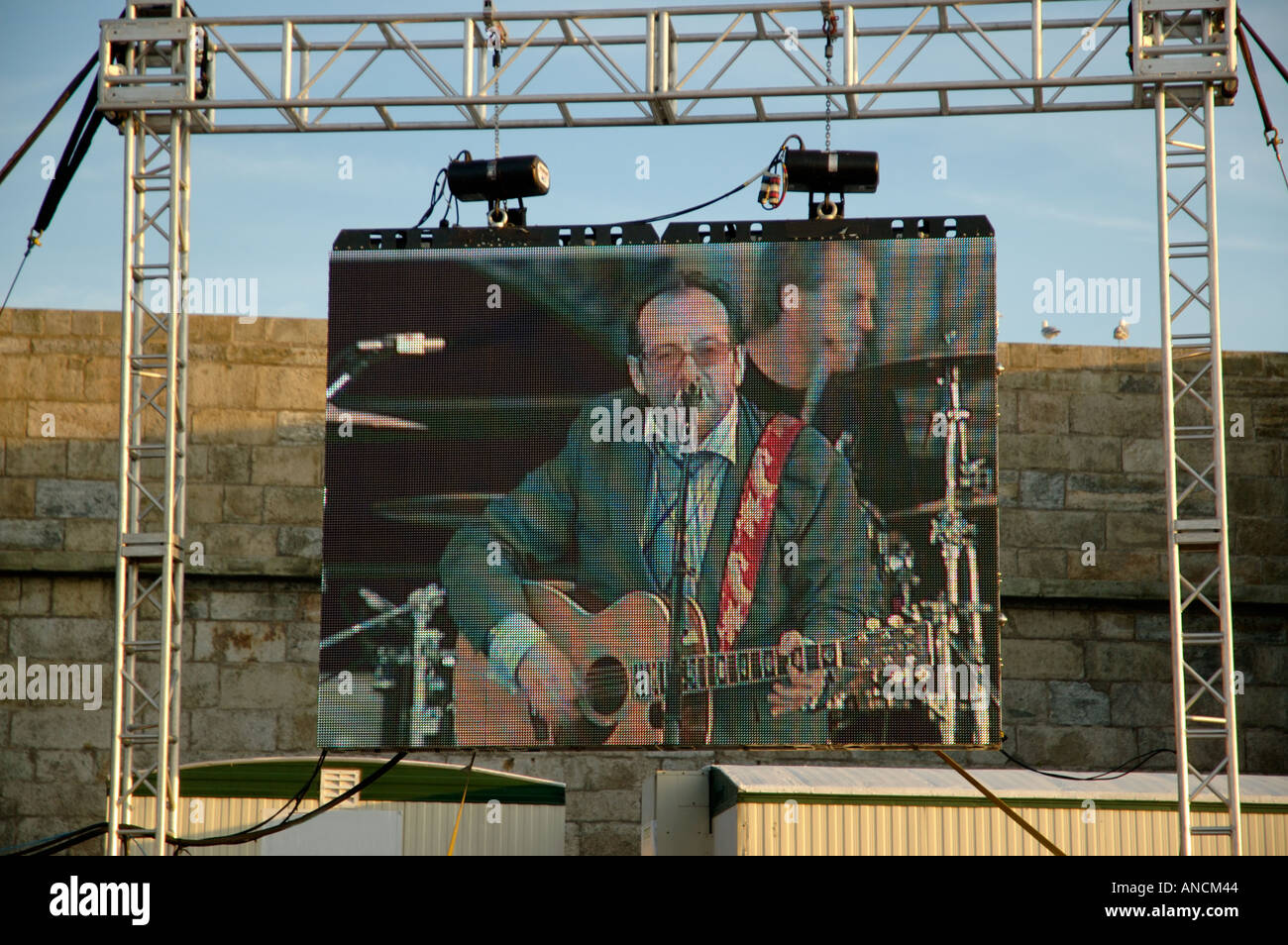 Elvis Costello on a large screen at Newport Folk Festival Editorial use only - Stock Image