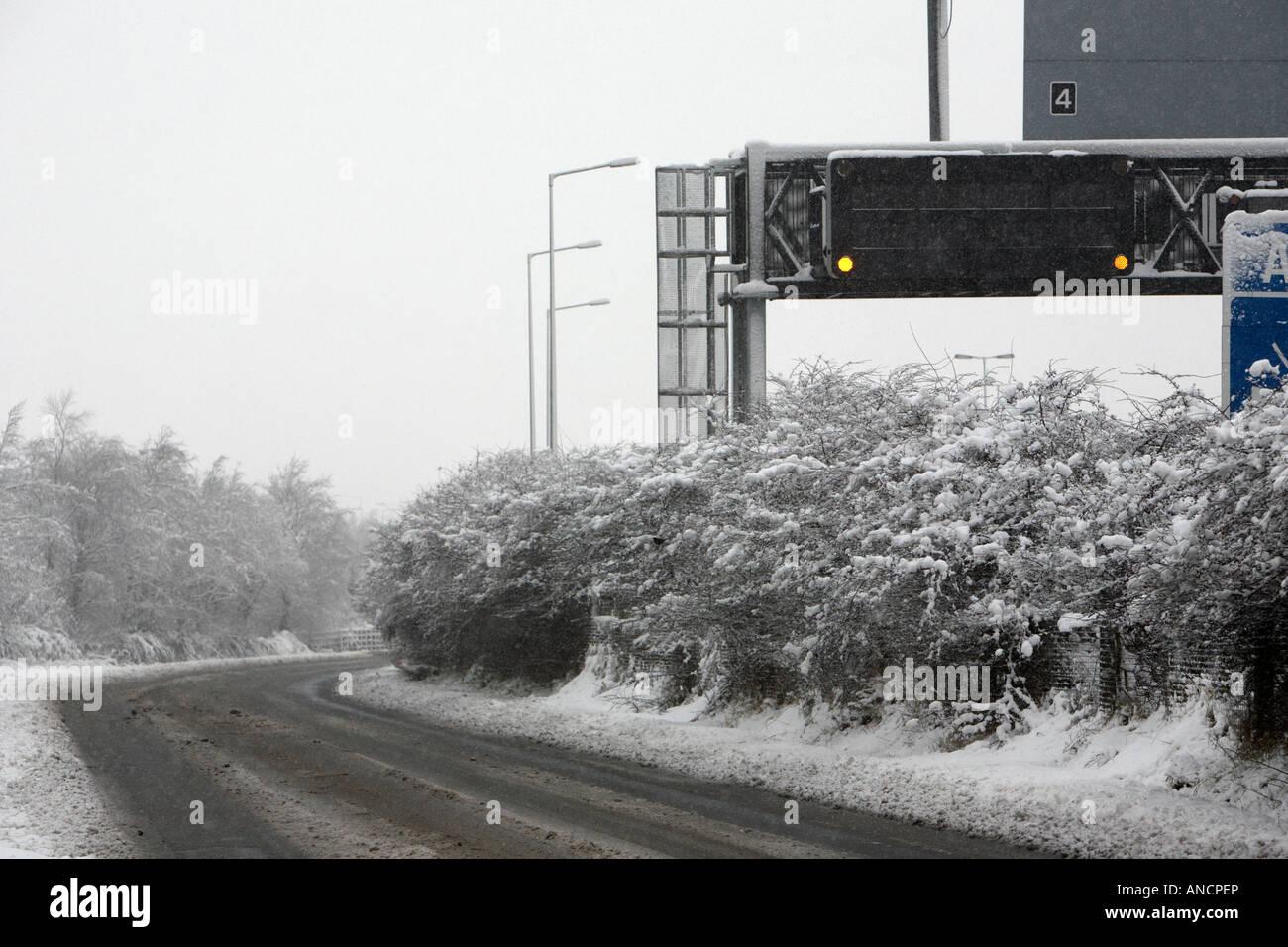 empty snow slush covered road next to motorway warning sign - Stock Image
