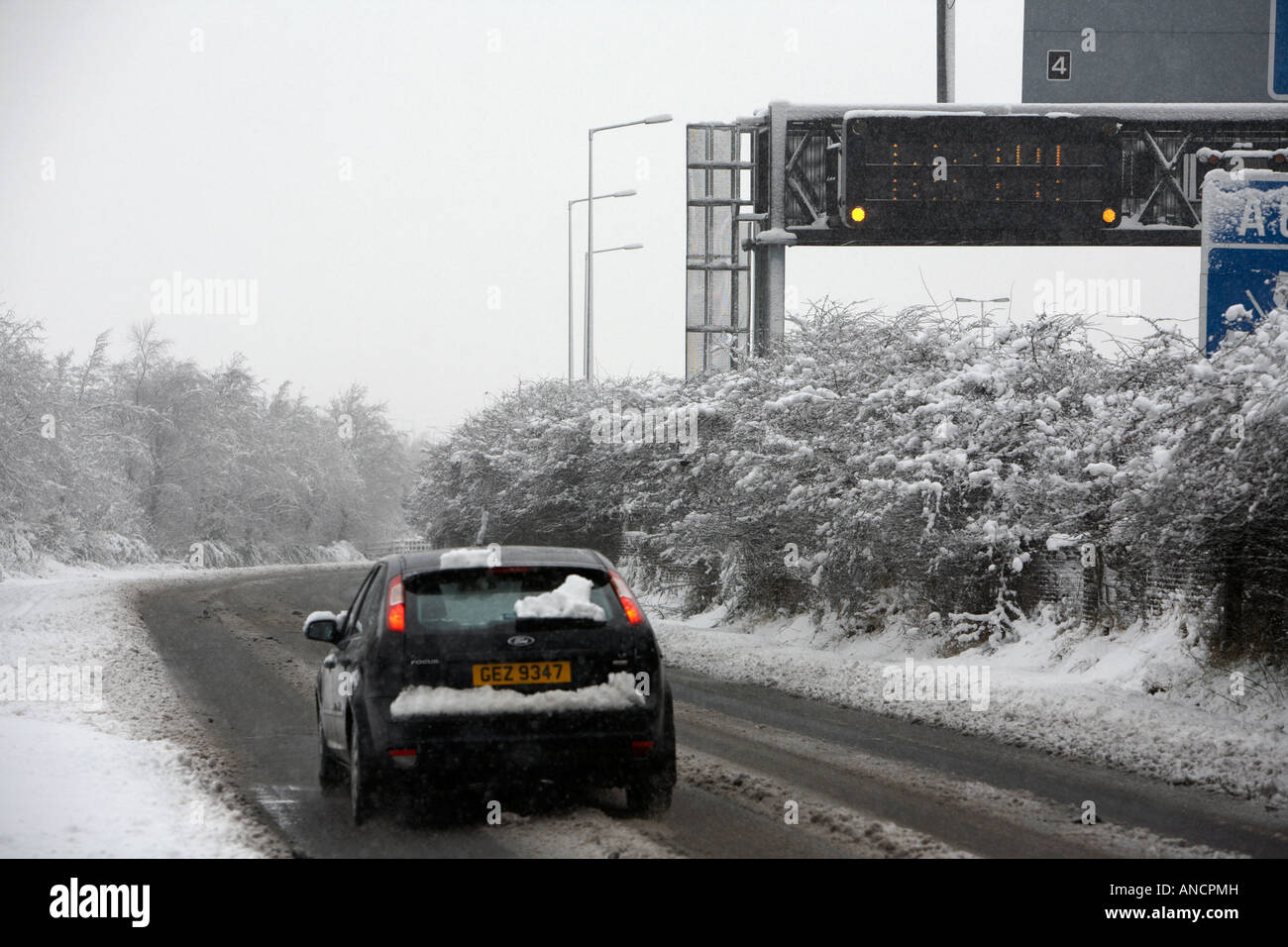 ford focus car driving along treated road next to motorway warning sign - Stock Image