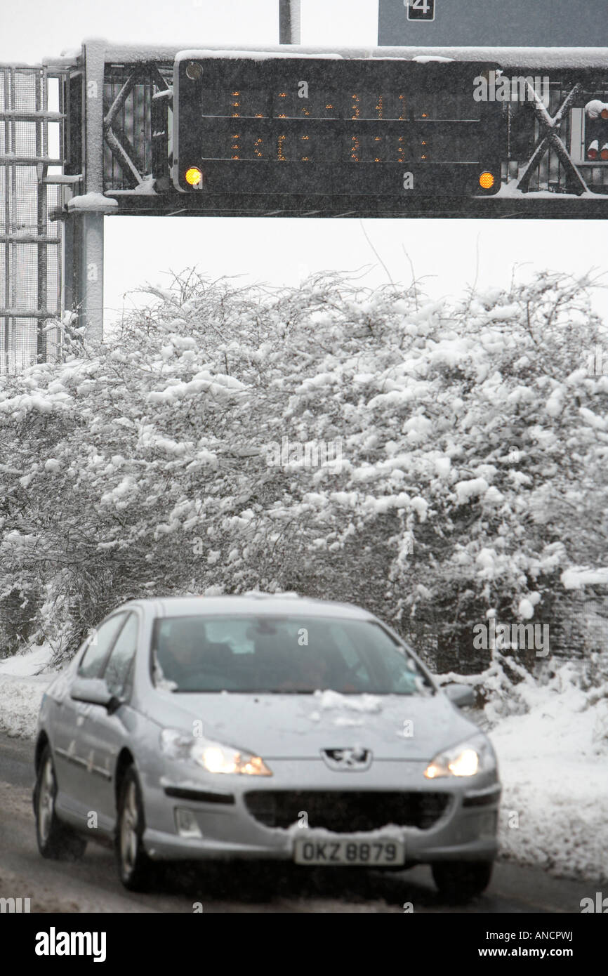 peugeot car with headlights on driving along treated road beside motorway warning sign - Stock Image