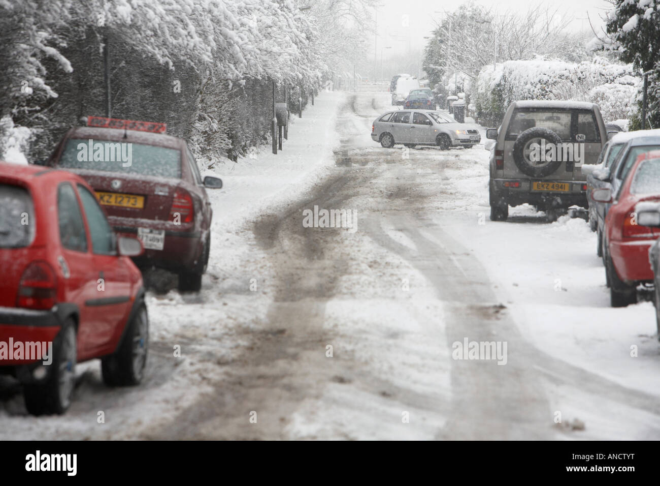 car spinning out of control on untreated icy road with other cars abandoned by the side of the road during snowstorm - Stock Image