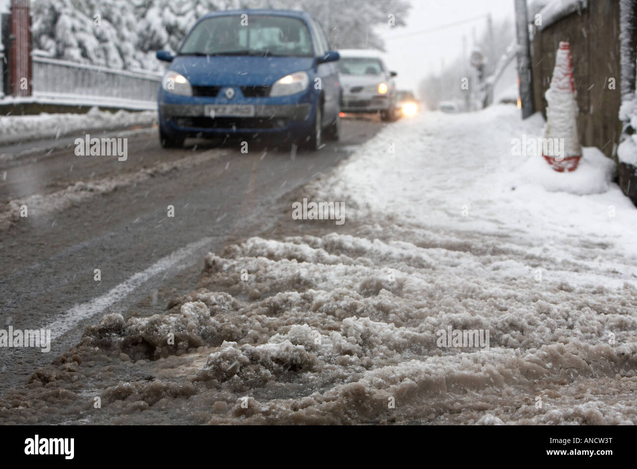 slush melting snow building up by the side of the road as cars travel past - Stock Image