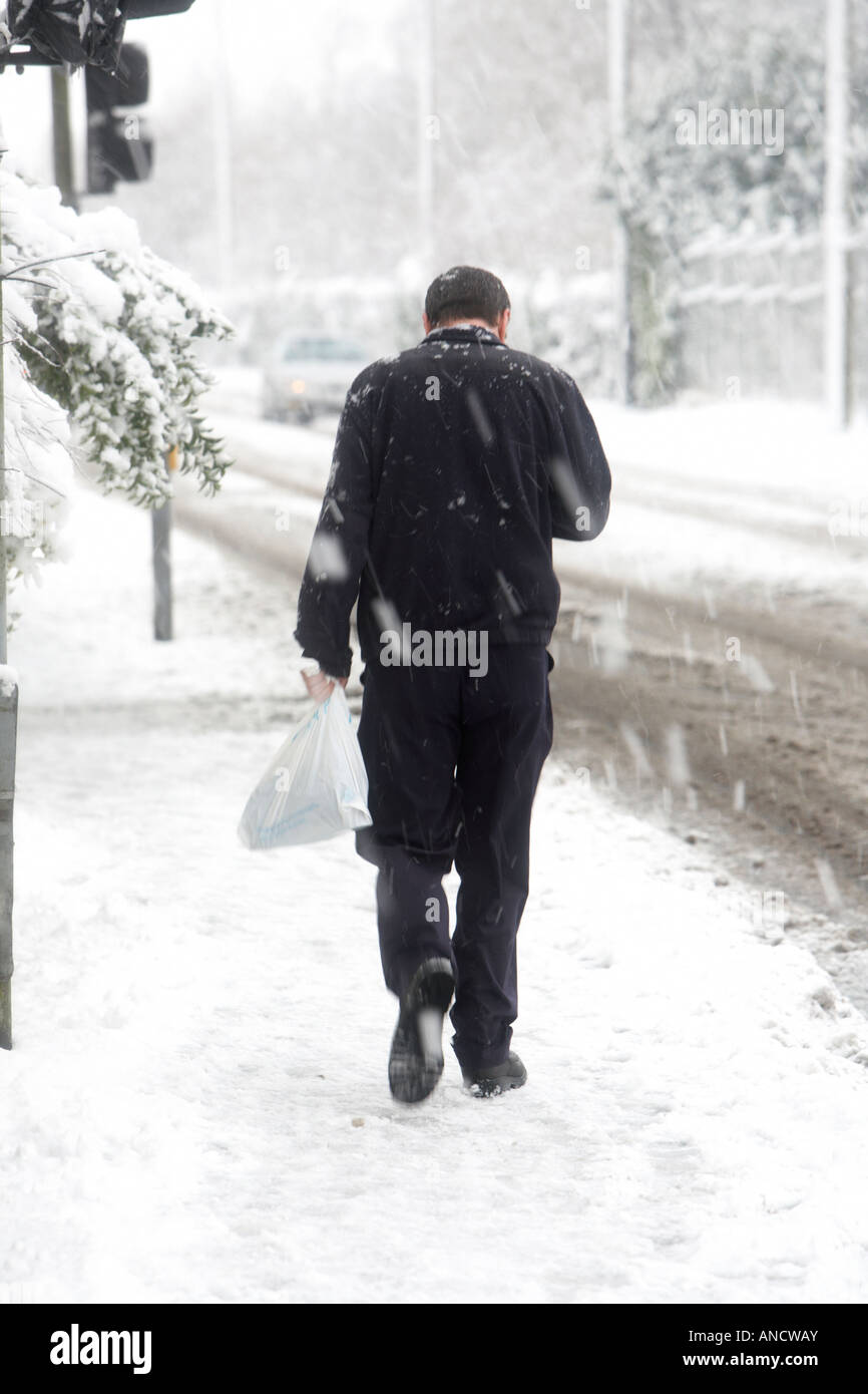 man with no hood walking uphill along snow covered footpath carrying plastic bag looking down at phone - Stock Image