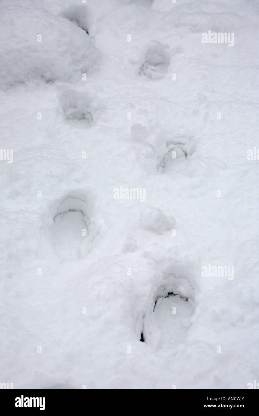 series of footsteps footprints in heavy snowdrift - Stock Image
