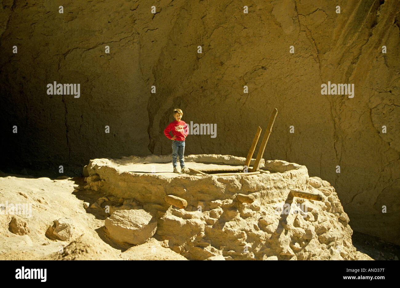 A young boy climbs into an ancient Anasazi kiva or religious chamber in a cave in Bandelier - Stock Image