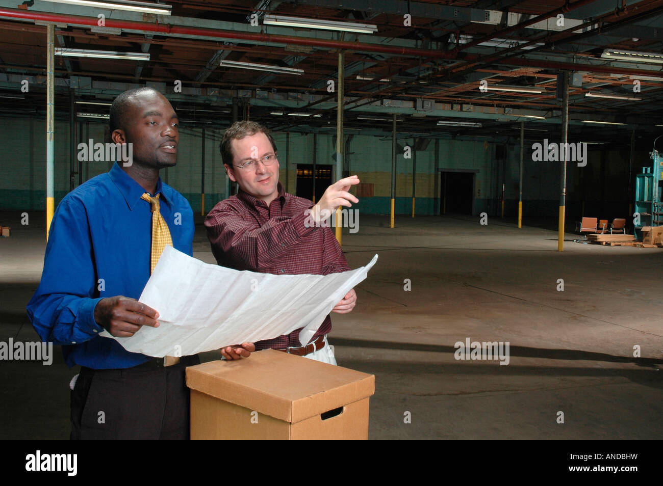 Two men in a empty factory or warehouse planning their entrepreneurial future - Stock Image