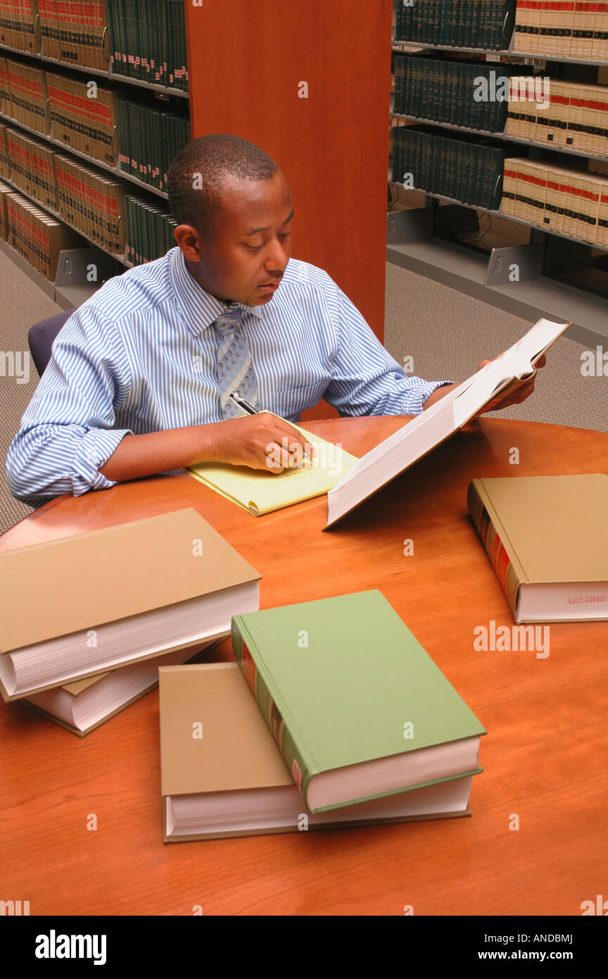 a black lawyer or college student studying researching law books of