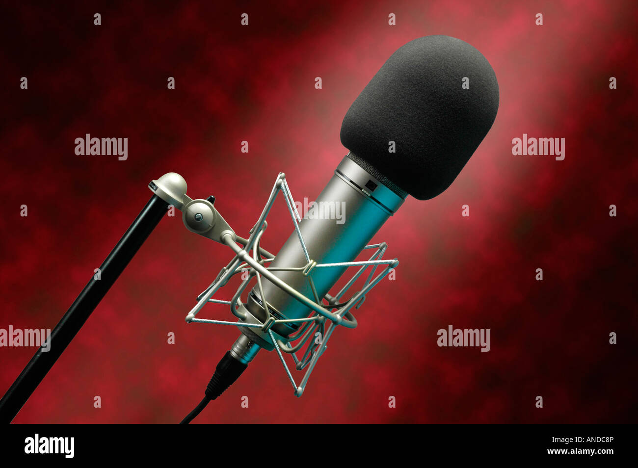 Professional studio microphone for voice or music recording against a red mottled background - Stock Image