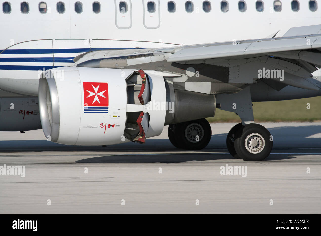 Close-up of a CFM56 turbofan engine nacelle on an Air Malta Airbus A320 jet plane with thrust reversers activated - Stock Image