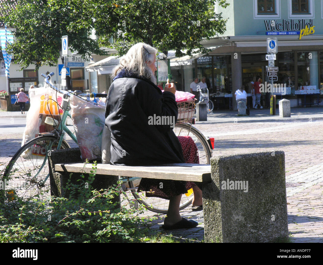 Old woman lonely lonesome social problem Bayern Bavaria german germany park square poor poverty moneyless - Stock Image
