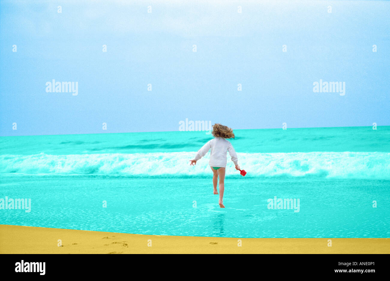 Young girl having fun running into the sea France - Stock Image