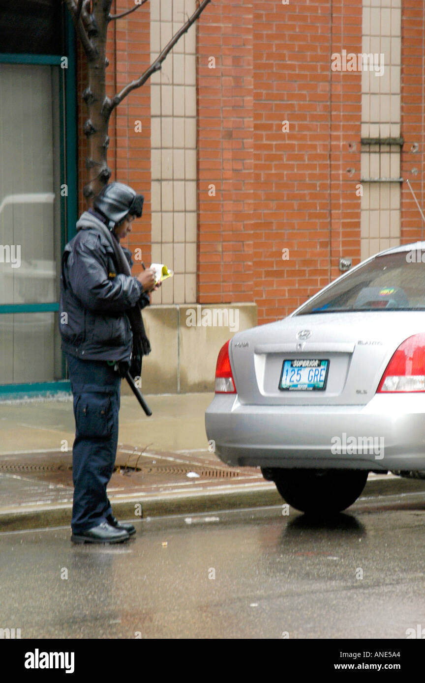 Ethnic Police Woman Issues Parking Ticket Violation - Stock Image