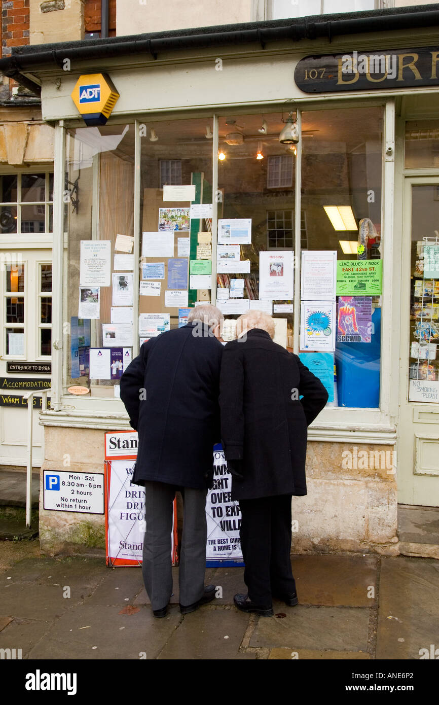 Couple browse the window of a newsagent s shop at Burford in the Cotswolds United Kingdom Stock Photo