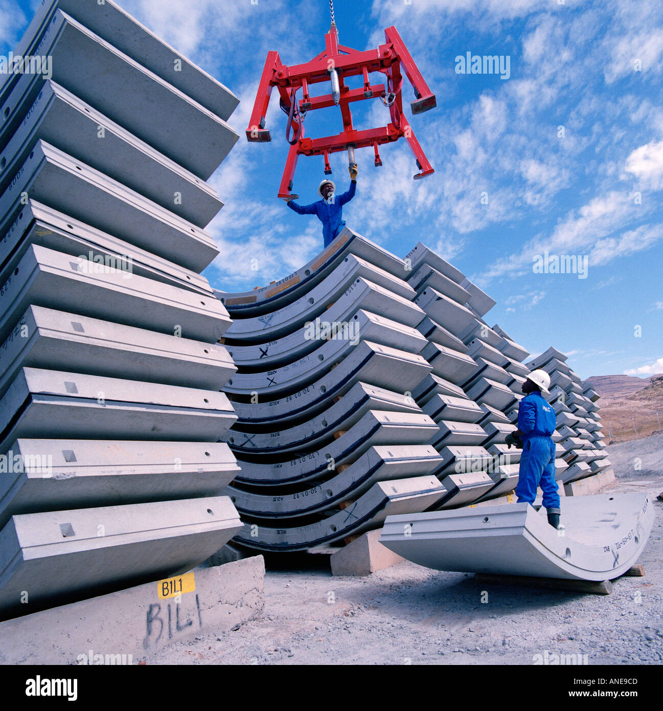 Workers stacking pre-cast steel reinforced concrete  segments used to line a tunnel on the Lesotho Highlands Water Project - Stock Image