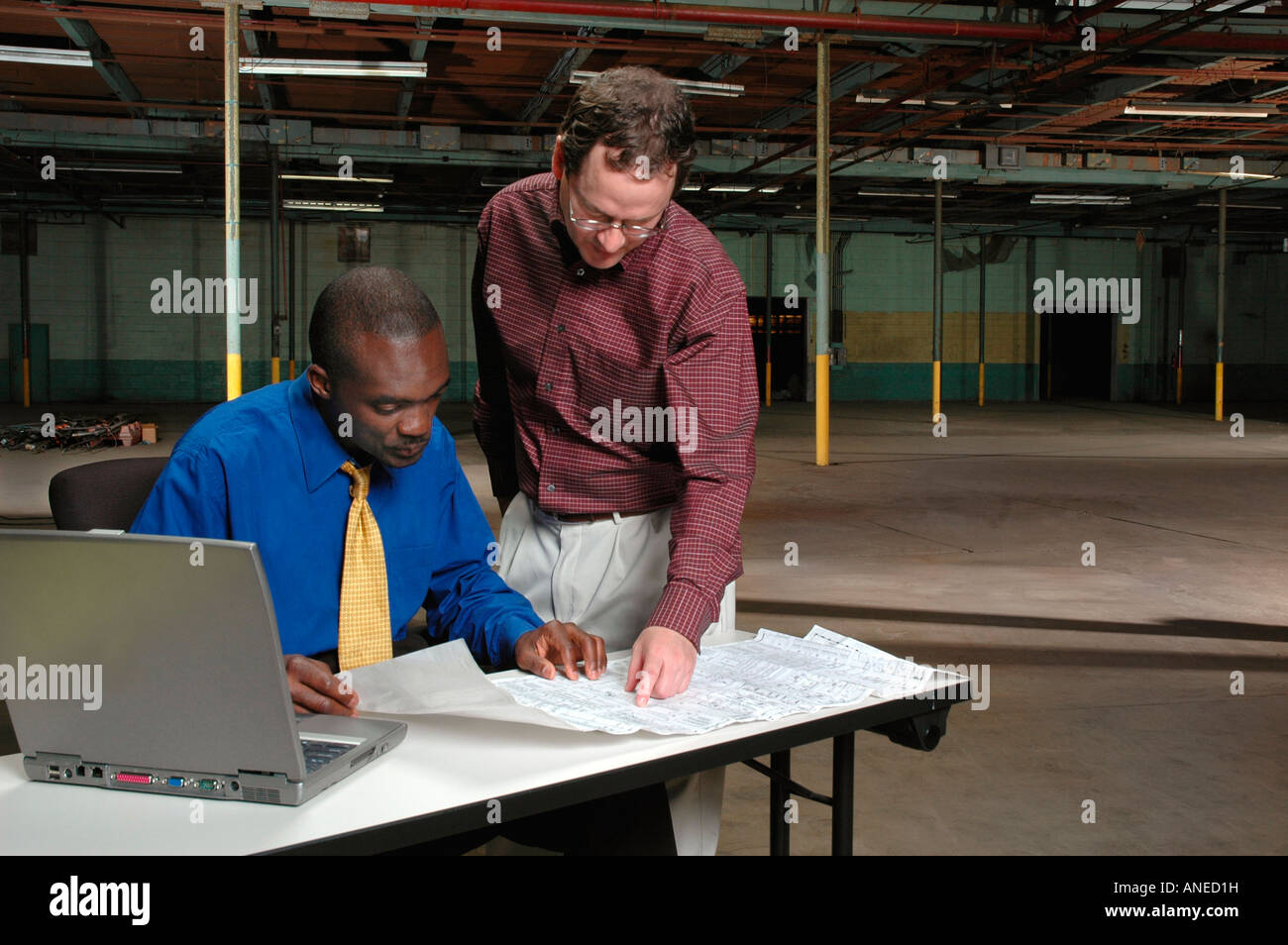 Two entrepreneurs reviewing a blueprint planning a new business - Stock Image