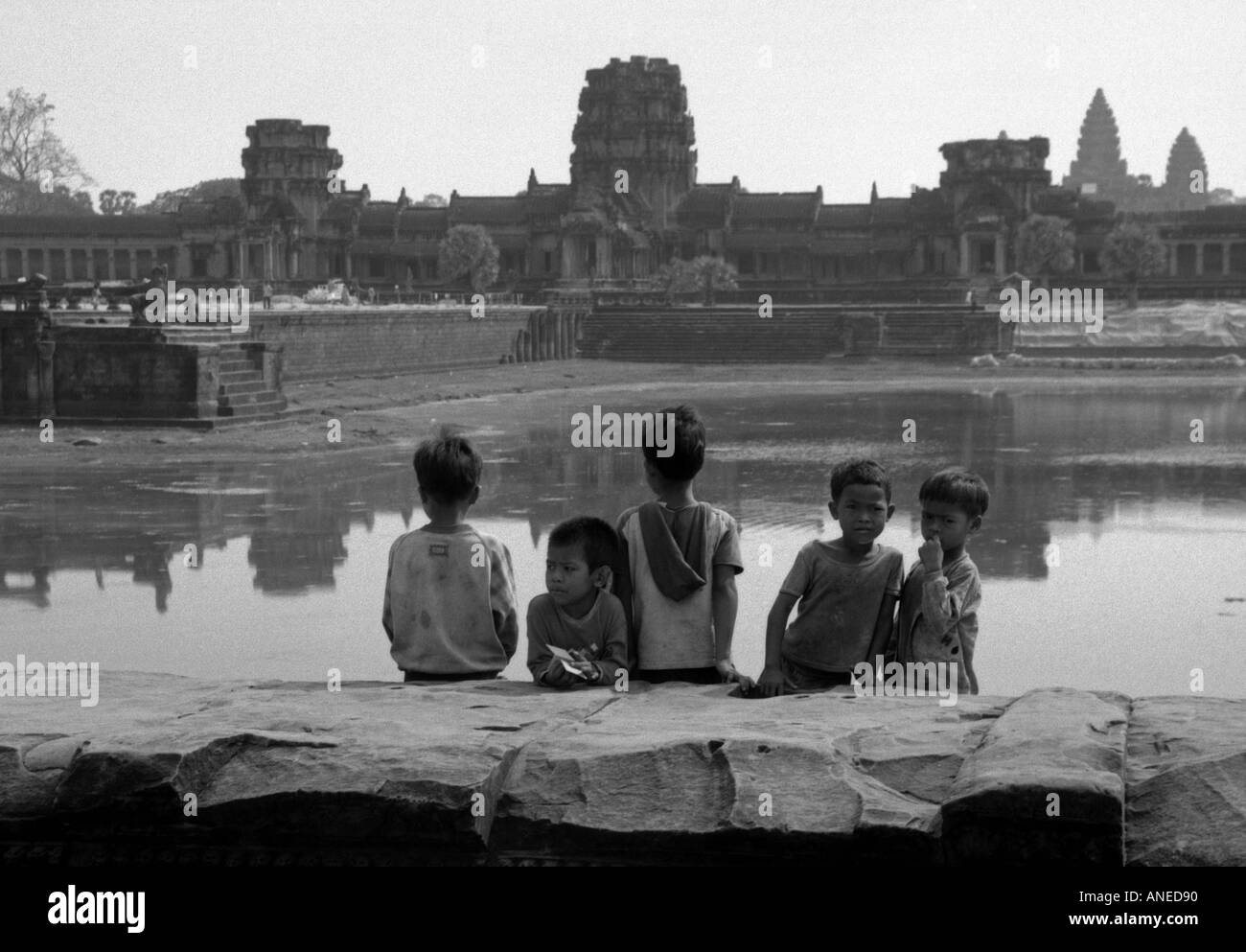 Portrait group indigenous boy sit outdoor look watch huge ancient site reflection water Angkor Wat Cambodia Southeast Asia - Stock Image