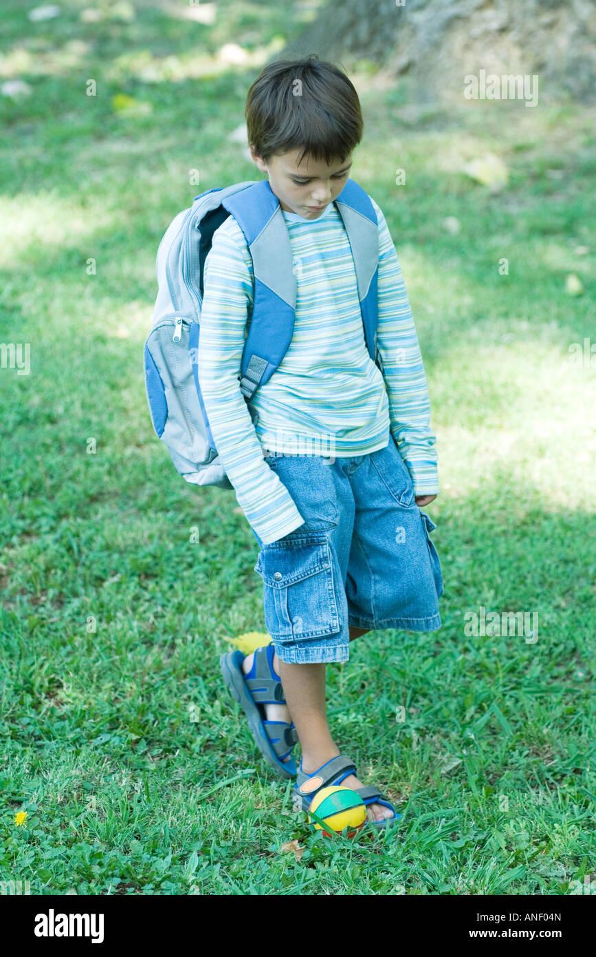 Boy walking across grass wearing backpack Stock Photo