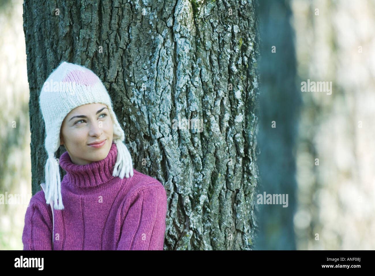 Young woman wearing knit hat, leaning against tree, smiling - Stock Image
