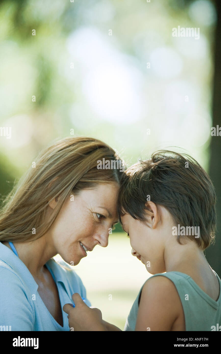 Mother and son talking with foreheads together, close-up - Stock Image