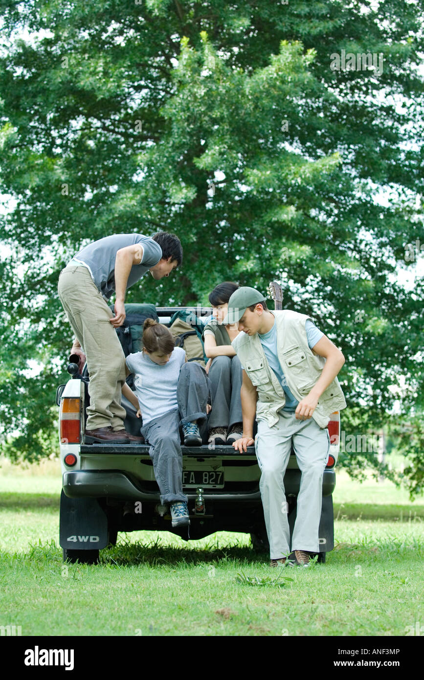 Hikers getting into back of pick-up truck - Stock Image