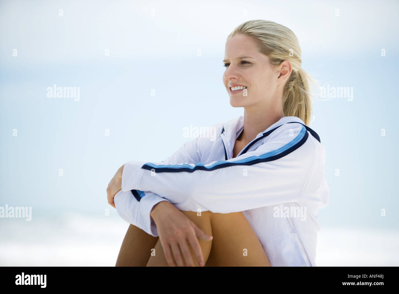 Young woman in active wear, sitting on beach, knees up, smiling - Stock Image