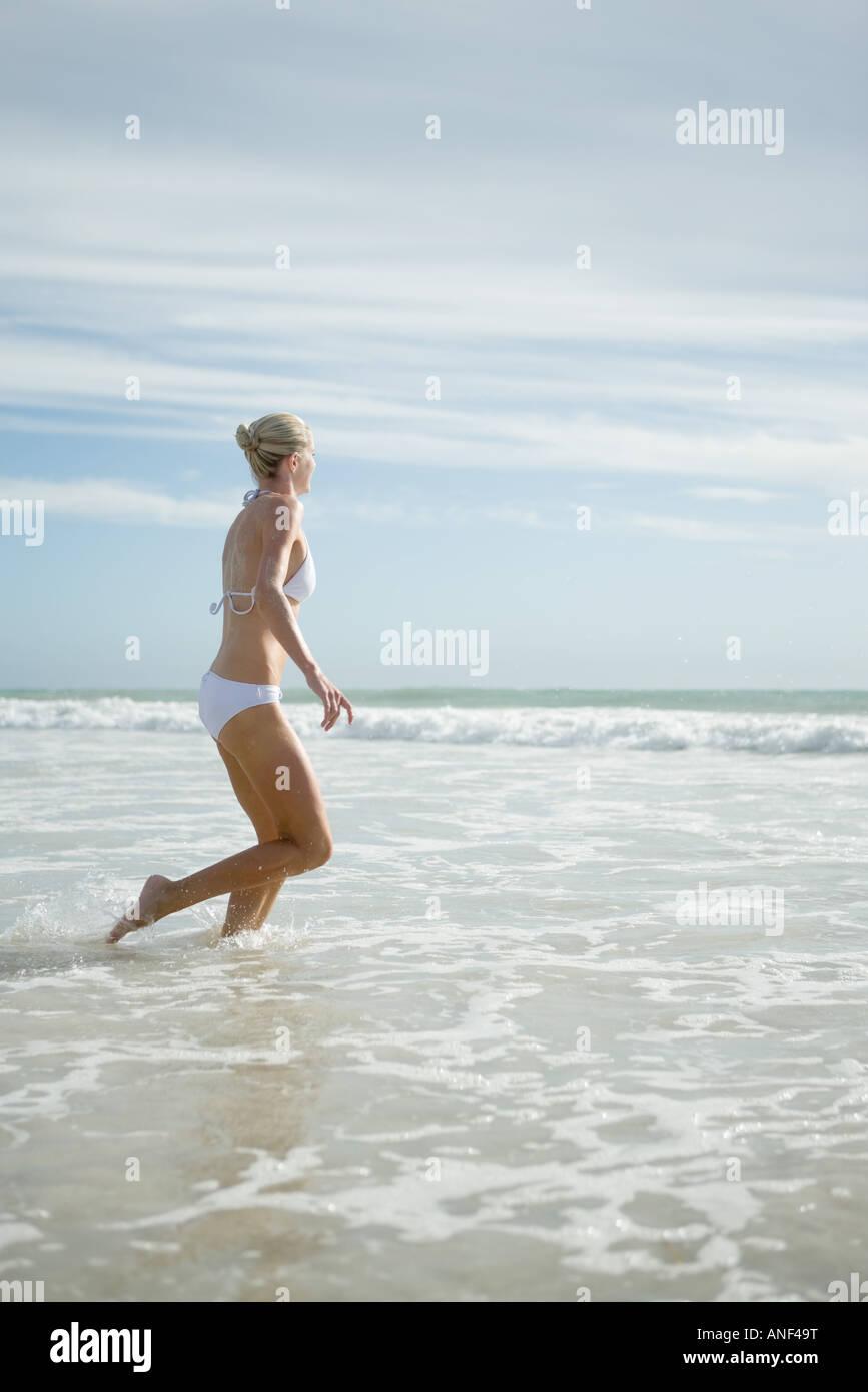 Young woman in bikini, running in surf - Stock Image