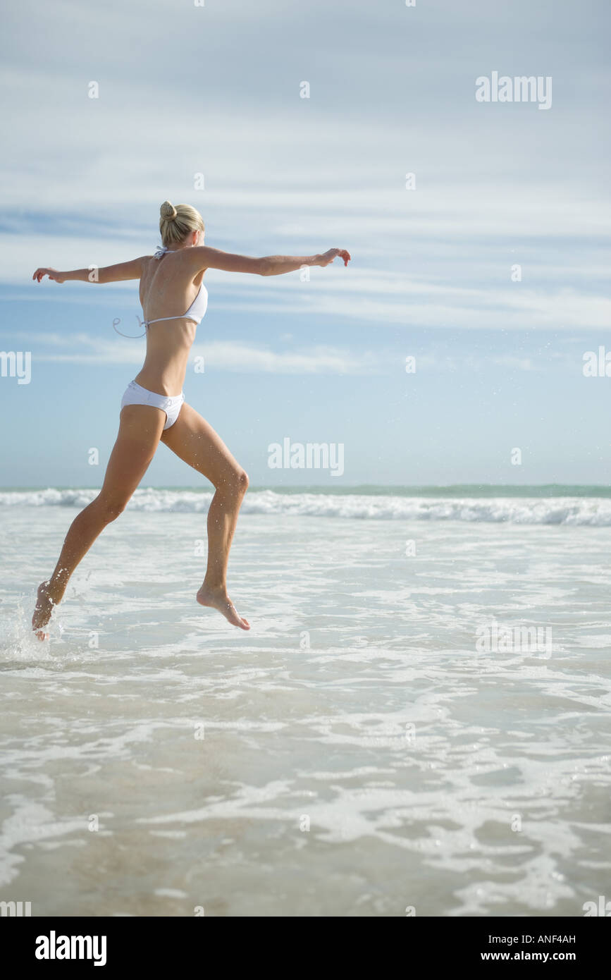 Young woman in bikini, leaping in surf - Stock Image