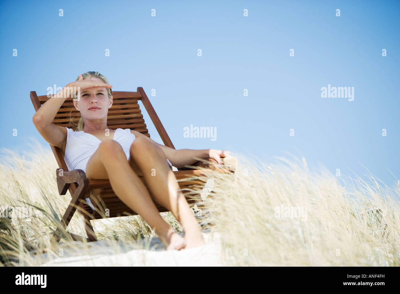 Young woman sitting in deckchair on beach, shading eyes - Stock Image