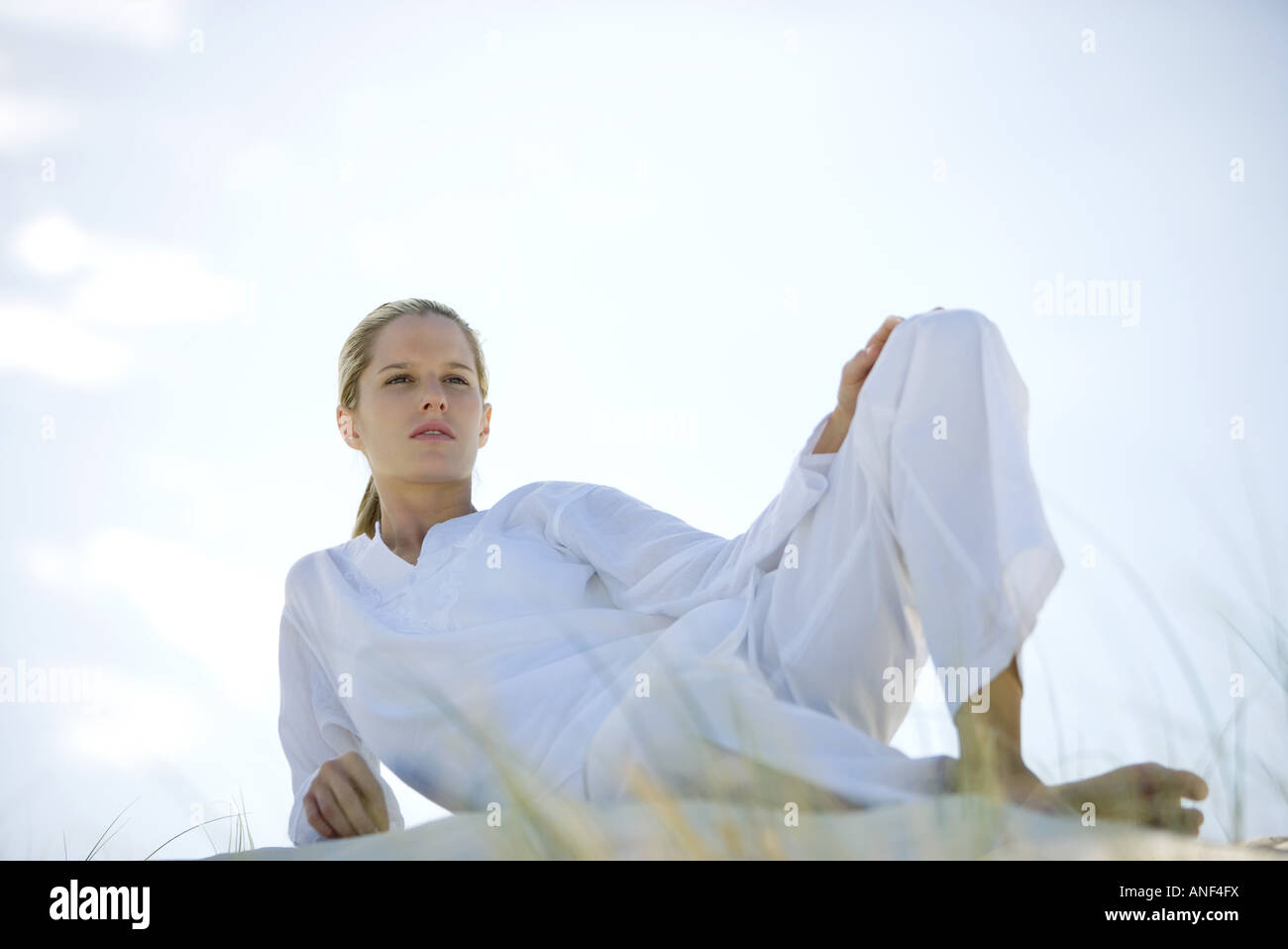 Woman lounging on dune, low angle view - Stock Image