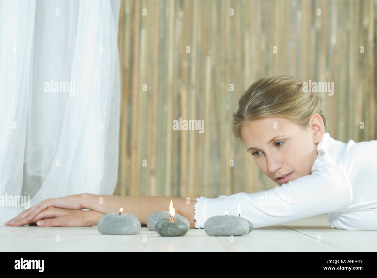 Woman lying on floor, looking at candles - Stock Image