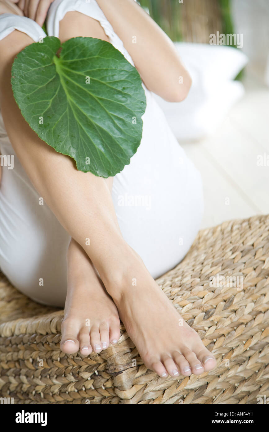 Young woman sitting with knees up holding leaf over legs, cropped view - Stock Image
