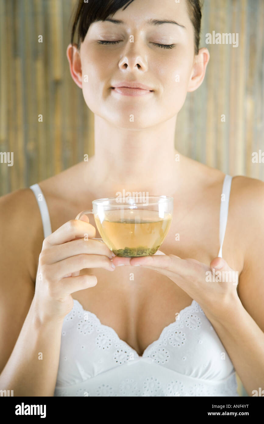 Young woman holding cup of herbal tea, eyes closed - Stock Image