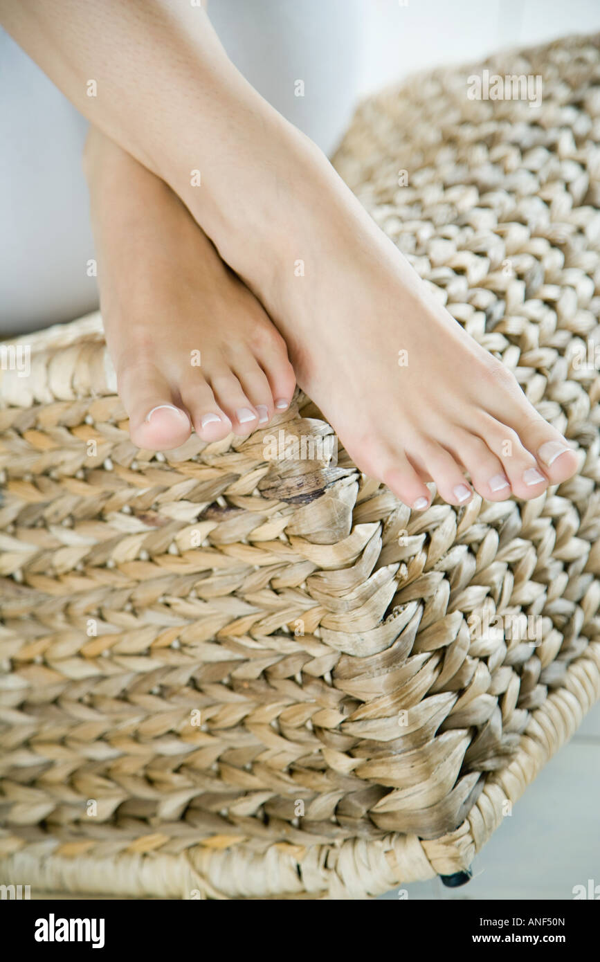 Woman's feet crossed on wicker seat, cropped - Stock Image