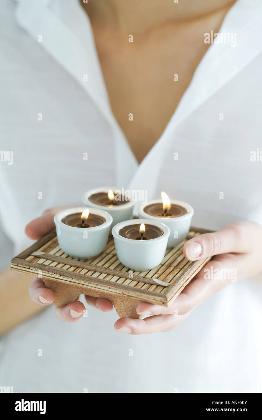 Woman holding tray of candles, close-up, cropped - Stock Image