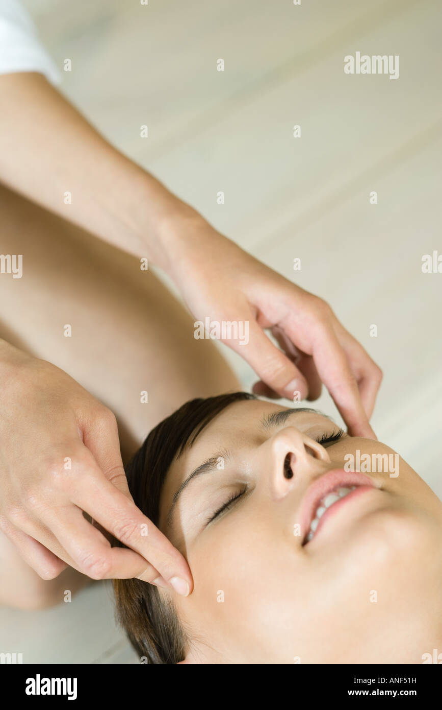 Young woman receiving head massage - Stock Image